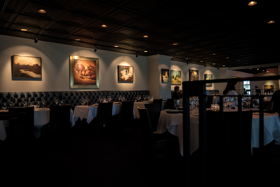Image of the Amerigo's Grille Terrazzo in dim lighting and surrounded by walls lined with paintings.