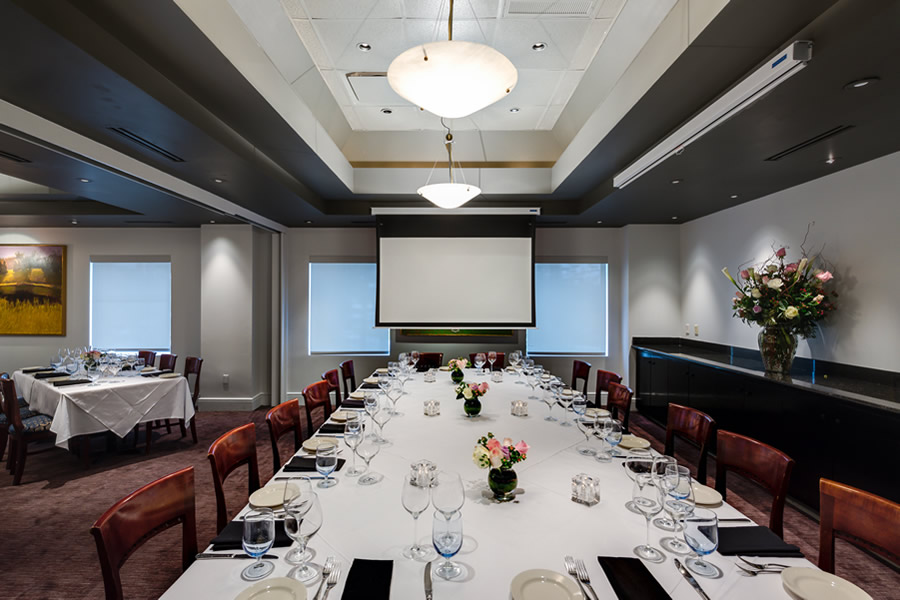 Image of the Amerigo's Grille Boardroom set for a private dining event with projector screen out.