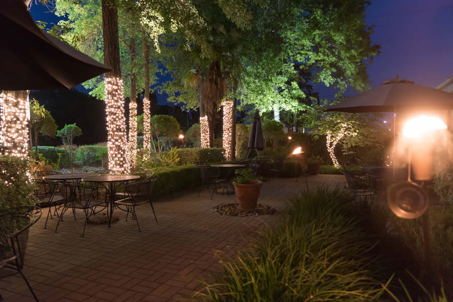 Image of the Amerigo's Grille Patio surrounded by trees decorated with Christmas lights.